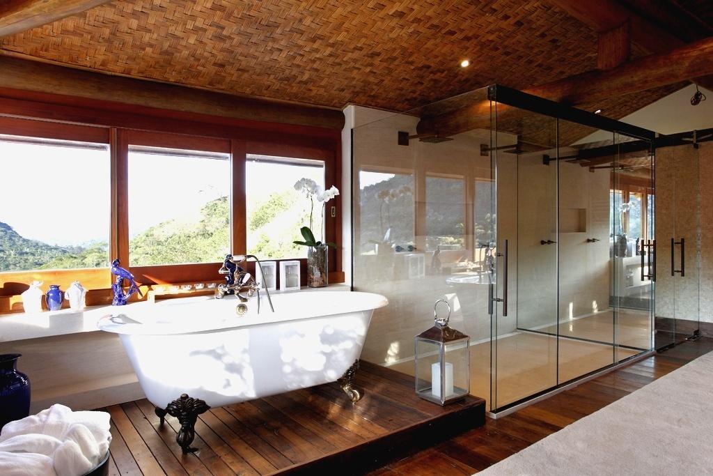 Conectada ao exterior por janelas envidraçadas e transparentes, esta sala de banho idealizada pela arquiteta Debora Aguiar é um verdadeiro spa. Com 32 m², fica em uma casa na montanha e tem forro revestido de malaca trançada, que dá o tom intimista. À esquerda está a banheira romântica, que fica um lance acima do resto do banheiro