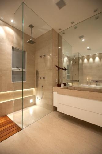 Deste ângulo do banheiro assinado pelo arquiteto Ricardo Rossi, um deck de cumaru separa os dois boxes e a bancada esculpida em Limestone é complementada por espelho até o teto. O local recebeu sonorização e automação da Antares