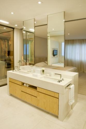 Esta sala de banho idealizada por Toninho Noronha tem 15 m² e une banheiro e closet no mesmo espaço. Piso e paredes foram revestidos por mármore crema marfil jateado. A bancada, em forma de ilha, separa o quarto do banheiro. Com duas cubas, ela funciona como pia e cômoda e os espelhos fixos no forro completam a seção 'beauté'