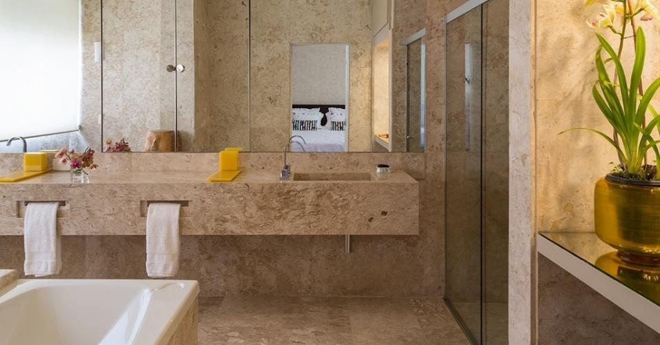 Inteiro revestido por mármore travertino, este banheiro 18 m² foi idealizado pelo arquiteto Ricardo Caminada e pela designer de interiores Daniela Berland Cianciaruso, do escritório Díptico. Com hidromassagem e bancada generosa equipada com duas cubas e toalheiros esculpidos, o ambiente é assistido também por um espelho que vai de ponta a ponta