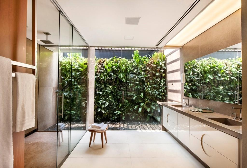 Neste setor do banheiro idealizado por Regina Adorno, está a bancada dupla também em mármore capuccino com cubas escavadas, servida por amplo espelho e armário laqueado da Ornare. Ao fundo, o jardim vertical da Vertia Paisagismo com um espelho d'água para manter o ambiente sempre fresco