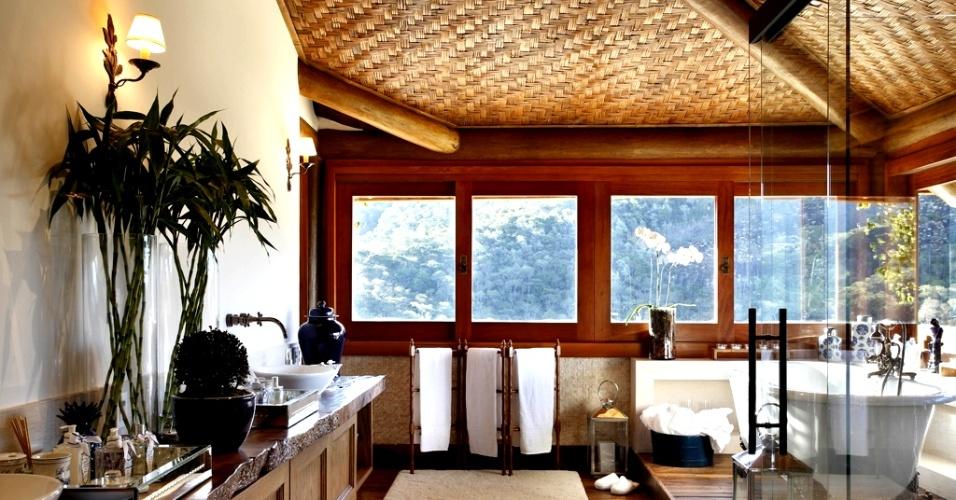O projeto assinado por Debora Aguiar conta com uma bancada generosa em madeira de demolição com cubas de apoio e bicas de parede com design retrô. No teto, as toras autoclavadas ficam à mostra e dão robustez ao banheiro. A iluminação natural que provém das janelas é vibrante pela manhã, quente à metade do dia e intimista ao entardecer, como diz a arquiteta