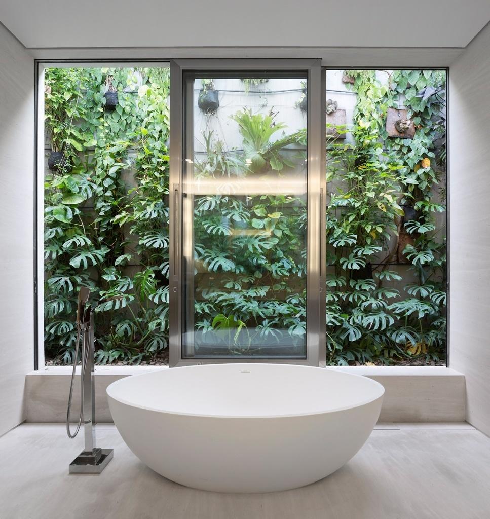 O banheiro idealizado por Fernanda Marques recebeu peças contemporâneas, como a banheira da Vallvé, seus metais e complementos. Atrás da porta de correr está o jardim vertical que tem como destaque as costelas-de-Adão