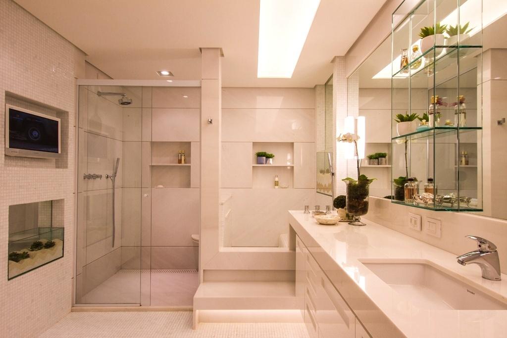O diferencial deste banheiro com 12 m², projetado por Cilene Monteiro Lupi, é o lavapés (à dir.) que fica em frente ao chuveiro, utilizado como área para descanso próxima a TV. Revestido de mármore, o espaço ganhou nichos envidraçados com plantas suculentas, que dão leveza ao ambiente