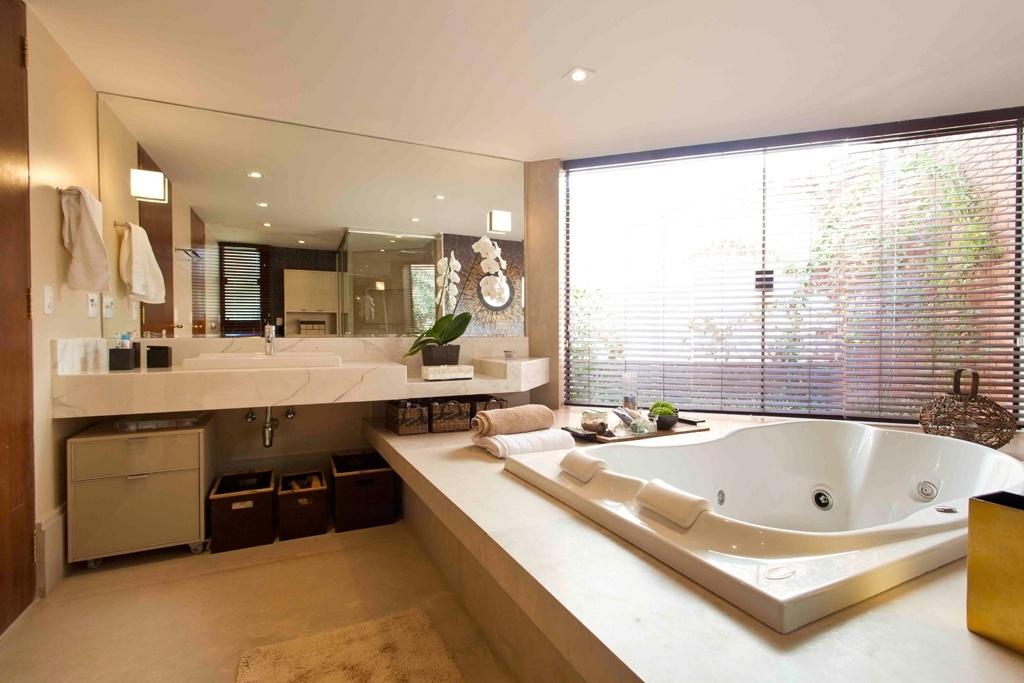 O projeto com 16 m² foi idealizado por Denise Monteiro e conta com janelas grandes voltadas para um jardim interno, que leva um pouco do verde aos momentos de descanso. Deste ângulo vê-se a bancada de mármore calacata e o spa com hidromassagem Jacuzzi embutida no patamar de Limestone, da Tamboré Mármores