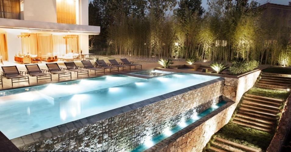 A piscina é cercada por decks de madeira em diferentes alturas e conta com iluminação cênica. O ambiente é protegido por formações de bambu taquara, pensadas pelo paisagista Alex Hanazaki