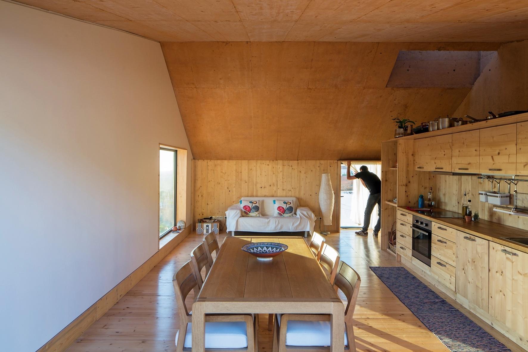 A cozinha da Casa do Zé fica integrada às salas de jantar e estar, ocupando o terceiro pavimento do monolito residencial, estruturado em concreto armado. Todos os revestimentos interiores, além dos armários são de madeira reciclada, reaproveitada das fôrmas de concretagem da fachada. No final da tarde, a janela (à esq.) traz para o interior da residência, a paisagem das vinhas do Vale Barris, banhadas pela luz do sol. A construção fica em Portugal e tem projeto do escritório Paratelier