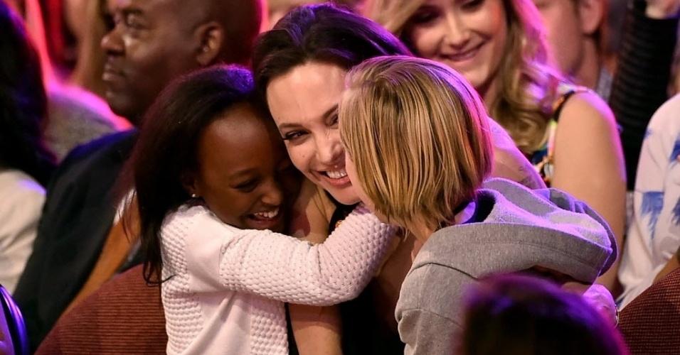 28.mar.2015 - Angelina Jolie é abraçada pelas filhas Zahara (à esq.) e Shiloh, ao vencer a categoria vilão favorito, por