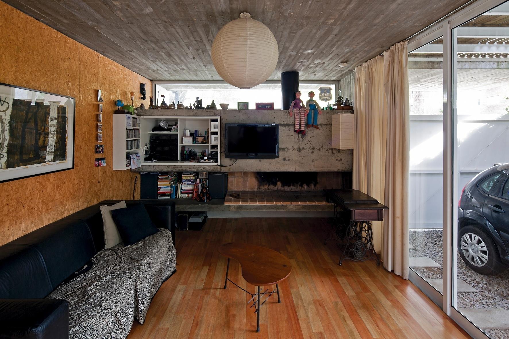 Na Casa Buceo, o estar está integrado ao corredor lateral externo, na altura da garagem. Com uma lareira à lenha, paredes revestidas por OSB (painel de tiras de madeira orientadas) e piso de madeira, o cômodo é sombreado, pois está protegido pela laje da varanda suspensa. A luz natural entra pela frente da casa, através de uma janela alta e delgada na fachada. A morada fica em Montevidéu, no Uruguai, e tem projeto de Marcelo e Martín Gualano