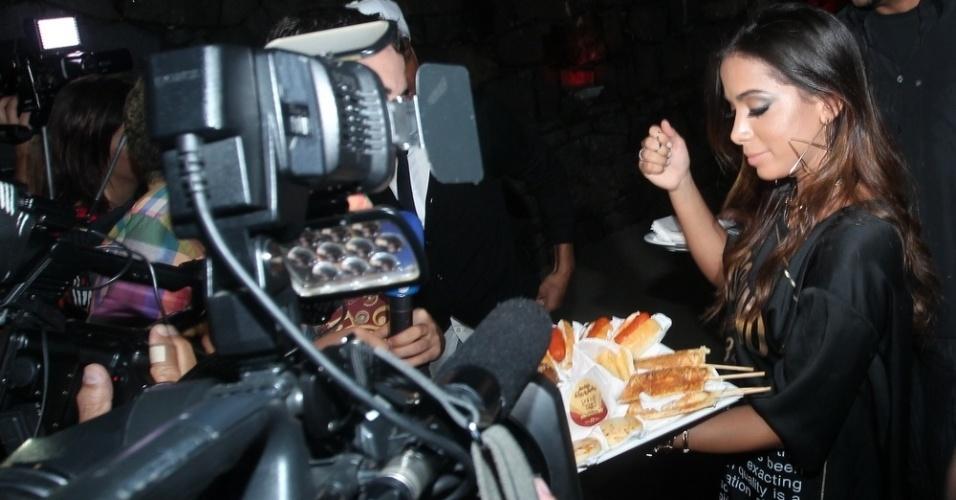 30.mar.2015 - Anitta serve hot dogs e guloseimas para os jornalistas na porta de sua festa de aniversário na Mansão Carioca, na zona sul do Rio de Janeiro, nesta segunda-feira
