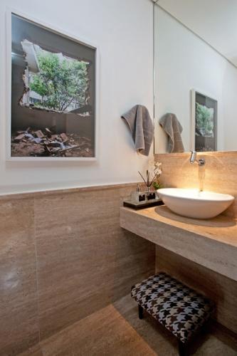 No lavabo, a parede e a bancada foram revestidas por mármore e, sobre a última, a cuba de apoio ganhou destaque pela iluminação. O projeto de interiores da casa em Campinas (SP) foi planejado pela arquiteta Elaine Carvalho