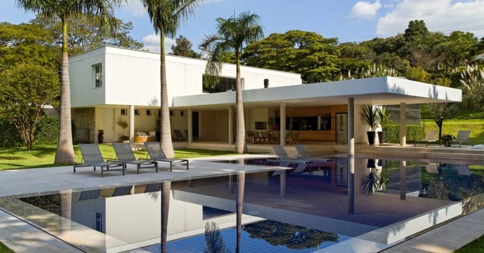 No bloco de lazer também está a garagem. Ela corresponde ao volume branco e mais alto da construção e está no mesmo nível da rua de acesso à casa LM/RM. Essa parte da construção, a vegetação e o desnível em relação à rua mantêm a privacidade dos usuários da piscina, pois não existe muro. A casa de campo fica em um condomínio no interior de São Paulo e tem projeto da arquiteta Cecilia Vicente de Azevedo