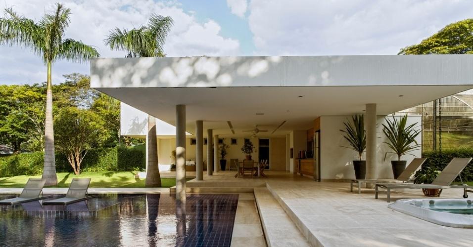 A arquitetura do bloco dos fundos (lazer) da casa LM/RM tem lajes planas, mas mantém os pilares em concreto aparente e os pisos de limestone. A sauna e os vestiários estão no mesmo nível da churrasqueira (à dir.). Por trás, no nível da rua, fica a garagem. A piscina é revestida com cerâmica 10 cm x 10 cm (Portobello), tem prainha e espreguiçadeiras em tela plástica e estrutura de aço inox. A casa no interior de São Paulo tem projeto da arquiteta Cecilia Vicente de Azevedo