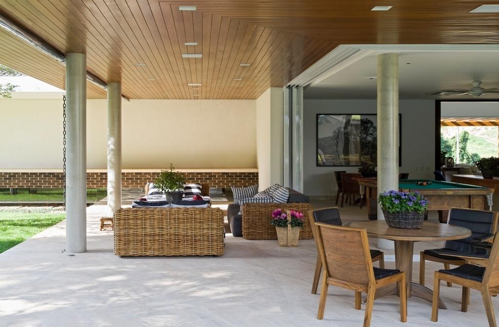 A casa LM/RM também conta com uma ampla sala de jogos - com bilhar e mesa para cartas - antecedida por mais uma varanda equipada com móveis de madeira ou vime. Em primeiro plano, a mesa redonda é do ateliê Carlos Motta. O refúgio de campo fica no interior de São Paulo e tem arquitetura do escritório CVA
