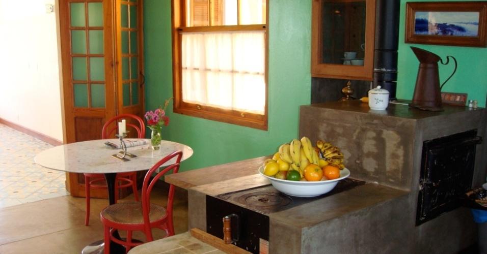 O fogão a lenha, em cimento queimado, ladeia o canto de almoço formado pela mesinha e as duas cadeiras Thonet e serve como aparador, quando não está sendo usado para a cocção. A cozinha de fazenda foi projetada pelo arquiteto René Fernandes