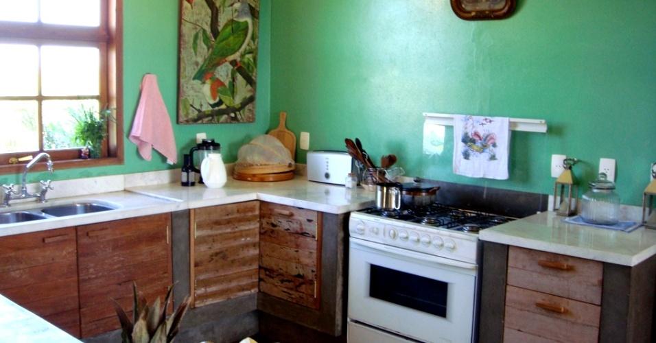 Nesta cozinha de fazenda com 20 m², o arquiteto René Fernandes aplicou verde nas paredes, que sustentam quadros antigos. O projeto conta, ainda, com armários arrematados por portas de madeira rústica