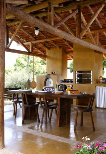Toda revestida por cimento queimado e com cobertura estruturada em eucalipto roliço, esta cozinha externa mede 110 m² e faz parte de um sítio. Projetado por Vilma Meirelles, o espaço tem arremates de tijolos no piso, que fazem o papel de juntas. O mobiliário robusto conta com mesa colonial e cadeiras da Isto é Brasil
