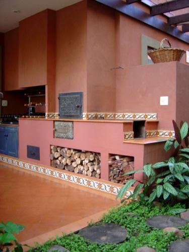 A cozinha externa e rústica, pensada pela arquiteta Paula Gambier, conta com fogão a lenha, forninho com tampa de ferro trabalhada e churrasqueira dispostos em linha. Os tozetos de ladrilho hidráulico e a pintura terra cal reforçam o estilo