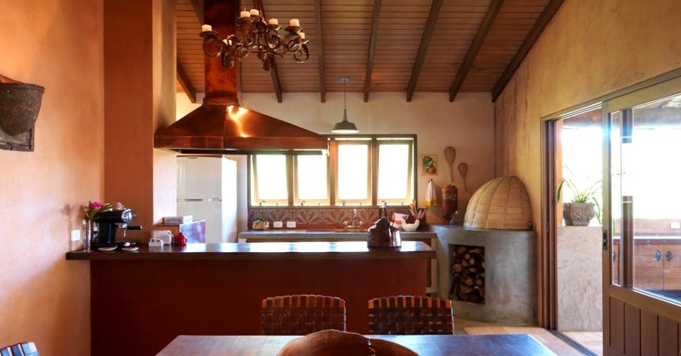 Nesta cozinha (35 m²) criada pelo arquiteto René Fernandes, a bancada ladeia o fogão a lenha, separando o setor de trabalho do de refeição. A coifa de cobre, suspendida pelo forro de madeira, dá charme ao ambiente e combina com o lustre. Nas paredes, o acabamento é feito com massa colorida e, no piso, os tijolos são de demolição. Repare: o corpo do forninho (à dir.) tem o bojo voltado para a cozinha e a boca para a área de lazer. A mesa e as cadeiras são do designer Carlos Motta
