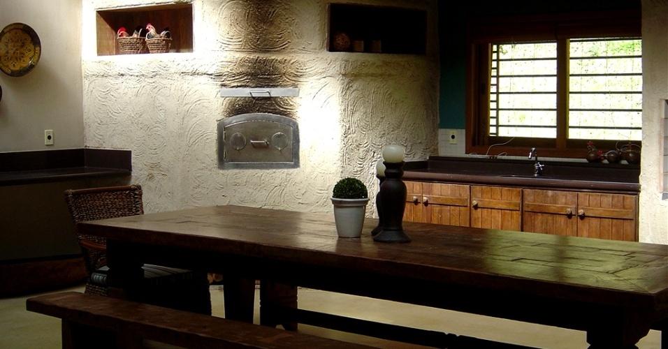 A cozinha faz parte do complexo de lazer com 90 m², idealizado pela arquiteta Paula Gambier, na sede de um sítio. O objetivo era oferecer maior aconchego à família e aos amigos, nas noites frias de São Roque (SP). As paredes texturizadas e caiadas formam nichos para apetrechos e enfeites e embutem o forno a lenha. A decoração rústica conta com móveis de madeira bem ao estilo