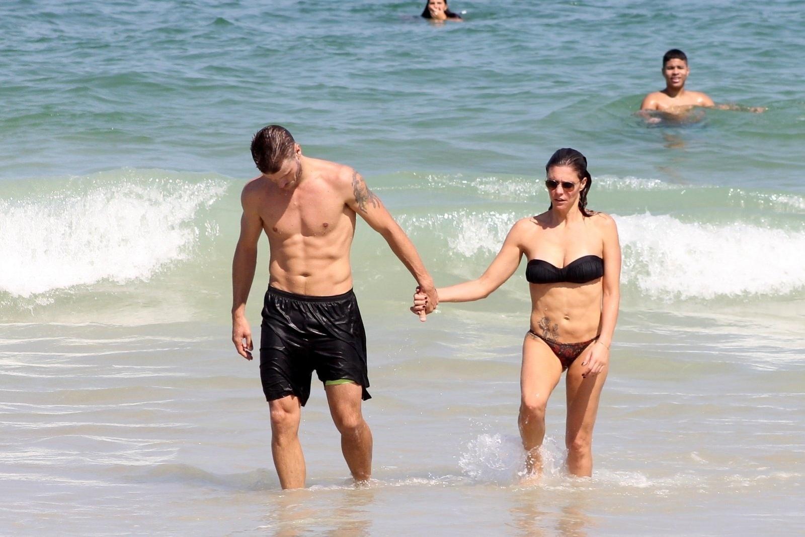 12.abr.2014 - Fernanda Lima e Rodrigo Hilbert deixam o mar de mãos dadas enquanto aproveitam dia na praia do Leblon, no Rio de Janeiro