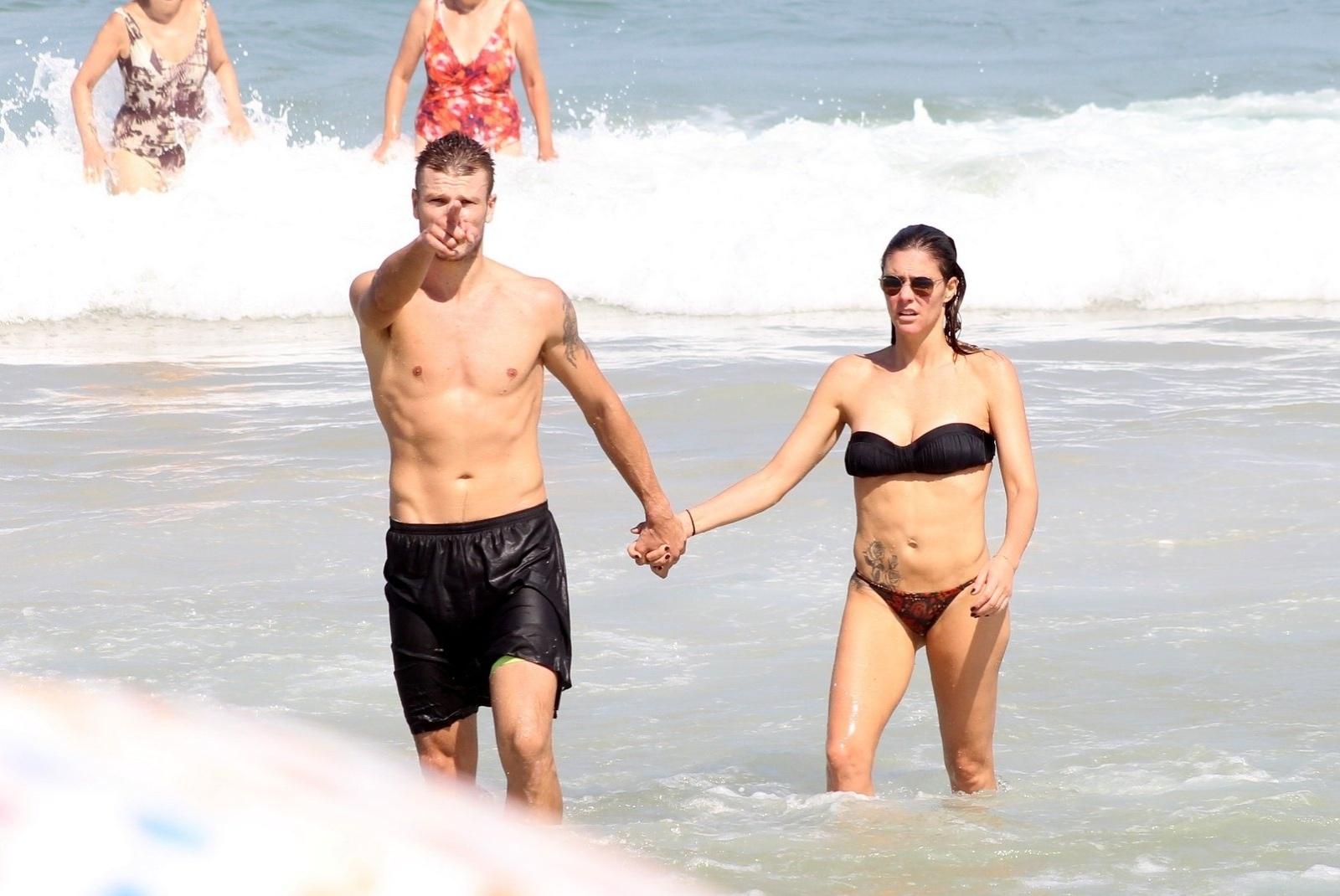 12.abr.2014 -Rodrigo Hilbert aponta para paparazzo enquanto deixa o mar de mãos dadas com Fernanda Lima, na praia do Leblon, no Rio de Janeiro