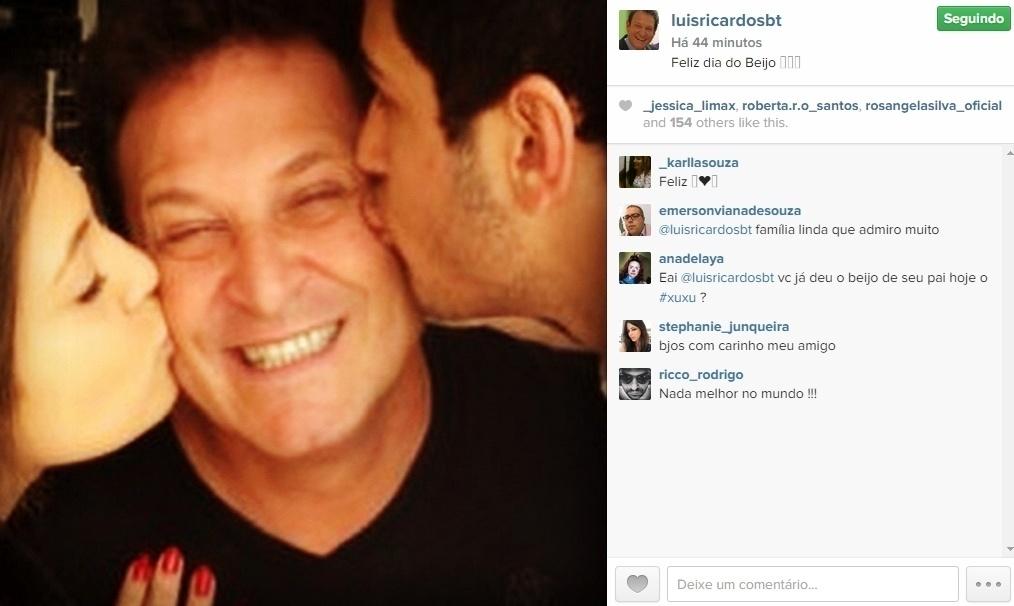 13.abr.2015 - O apresentador Luiz Ricardo fez questão de publicar uma foto nesta segunda-feira desejando um feliz Dia do Beijo aos fãs. Na imagem, ele aparece ganhando um beijo em cada bochecha dos filhos. Os seguidores elogiaram: