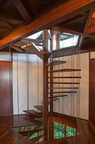 Apoiada na coluna central de madeira e por tirantes de aço, a escada com degraus de madeira perpassa todos os pavimentos da casa Tijucopava, projetada pelo arquiteto Marcos Acayaba