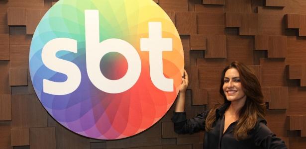 Ticiana Villas Boas posa ao lado do logo do SBT após assinar contrato com a emissora para apresentar um reality culinário
