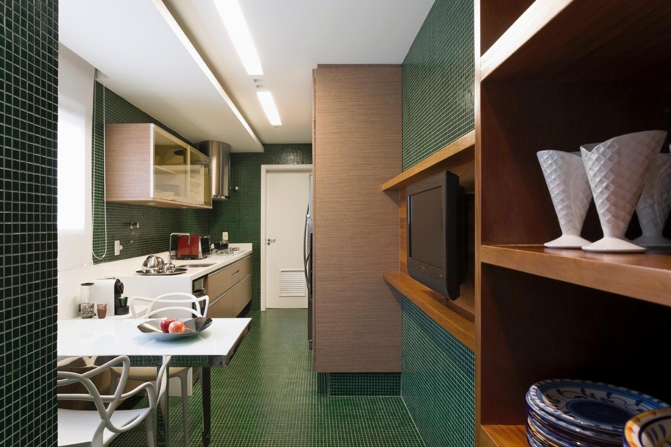Como uma caixa verde, a cozinha foi revestida inteiramente com pastilhas de vidro da Vidrotil. O painel da Tv e as prateleiras, ambos em peroba mica foram executados pela marcenaria Inovart e, os armários, pela Formaplas. O apê Panamby tem projeto de reforma do arquiteto Diego Revollo