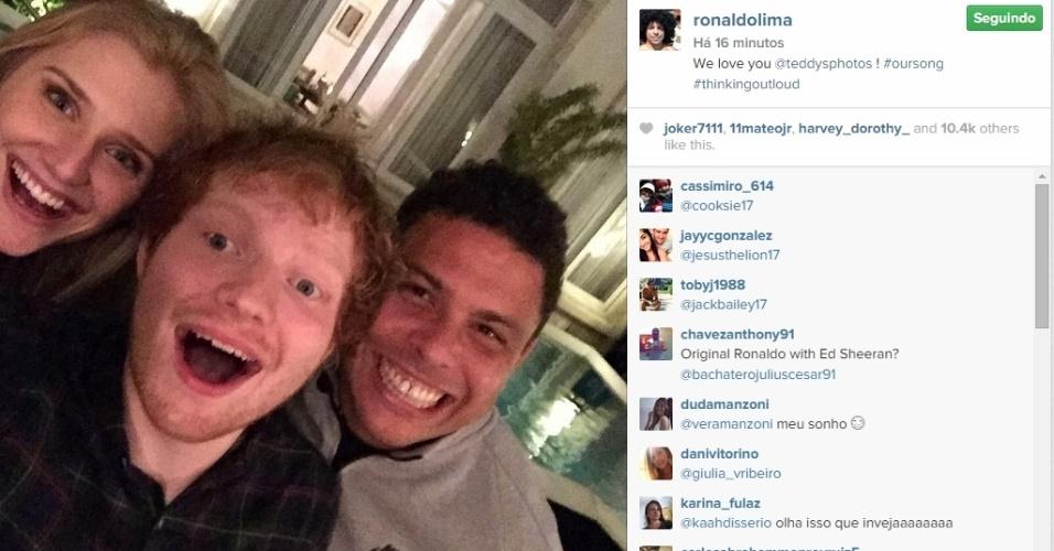30.abr.2015 - Ronaldo Fenômeno decidiu bancar o anfitrião e recebeu o cantor Ed Sheeran para uma festa em sua casa, na noite passada. Em foto publicada nesta quinta-feira, ele e a namorada, a modelo Celina Locks, aparecem sorridentes ao lado do cantor.