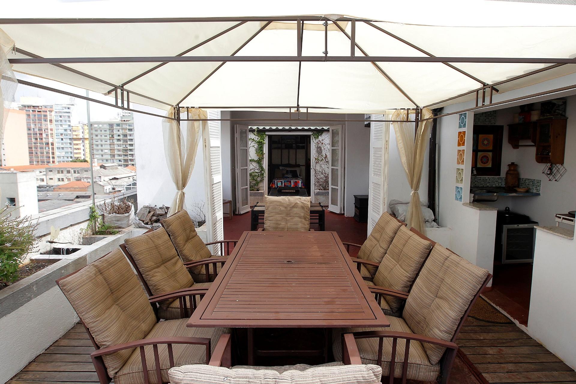 Sobre a cobertura do apartamento de Nico Puig, uma grande mesa de jantar fica protegida pela cobertura de lona e conta com uma pequena cozinha de apoio (à dir.). Ao fundo, um dos quartos de hóspede, com cama de solteiro. O dormitório também possui cozinha própria. O apê fica no centro de São Paulo