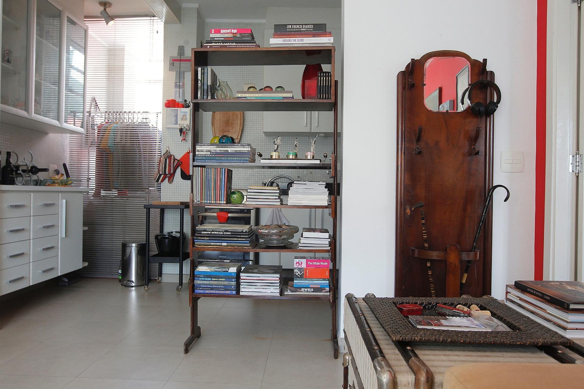 Na entrada da sala de estar do apê do ator Nico Puig, uma antiga chapeleira. Na cozinha ali ao lado, os móveis são novos e planejados. Para fazer a divisão dos ambientes, uma singela estante que apoia livros e outros objetos