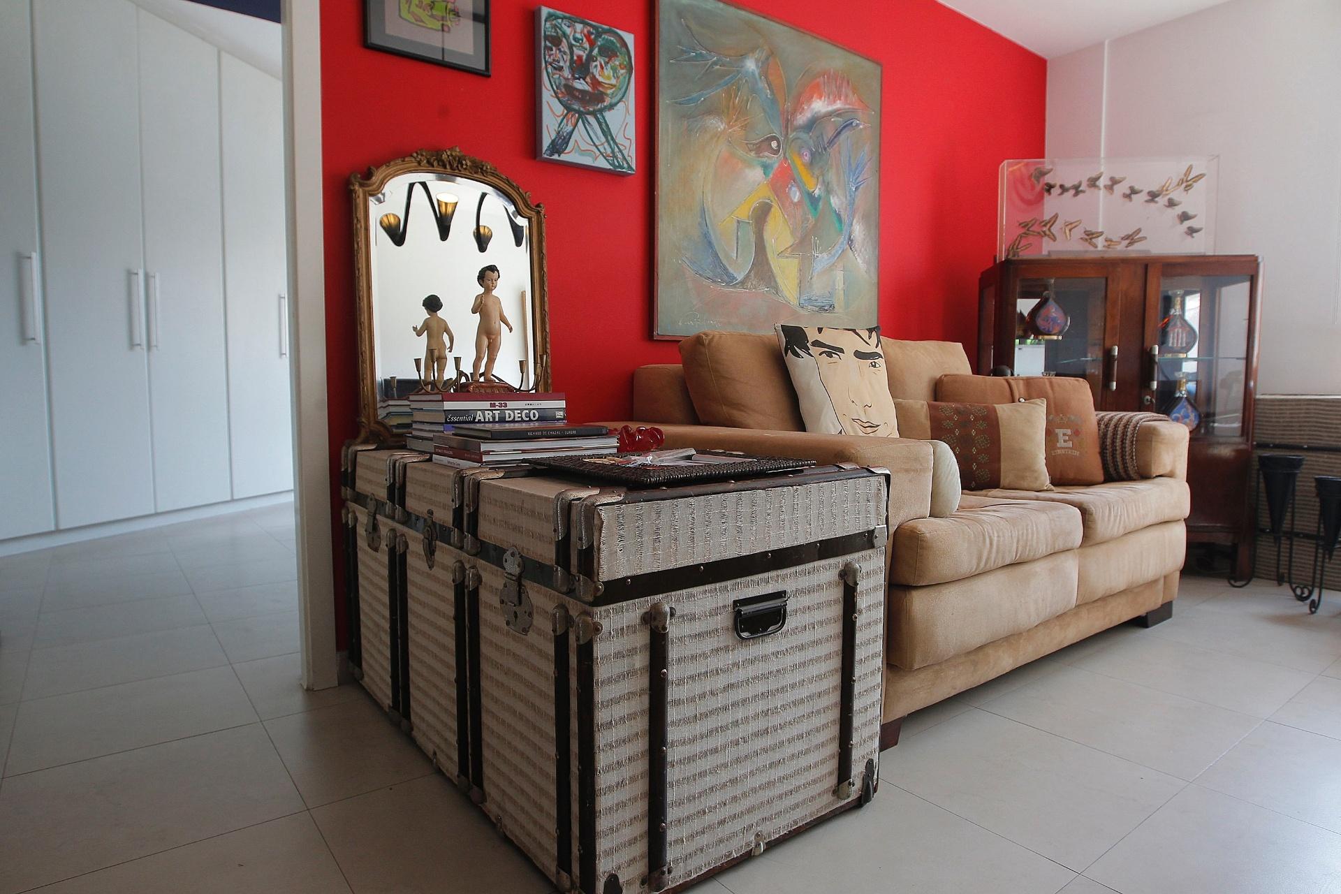 Na sala de estar do apartamento de Nico Puig, algumas peças reaproveitadas, como o velho baú, usado como apoio para o sofá. O revestimento foi feito com tecido de cortina velha. Sobre a cristaleira, o suporte de acrílico com borboletas foi comprado no lixo, por R$ 6