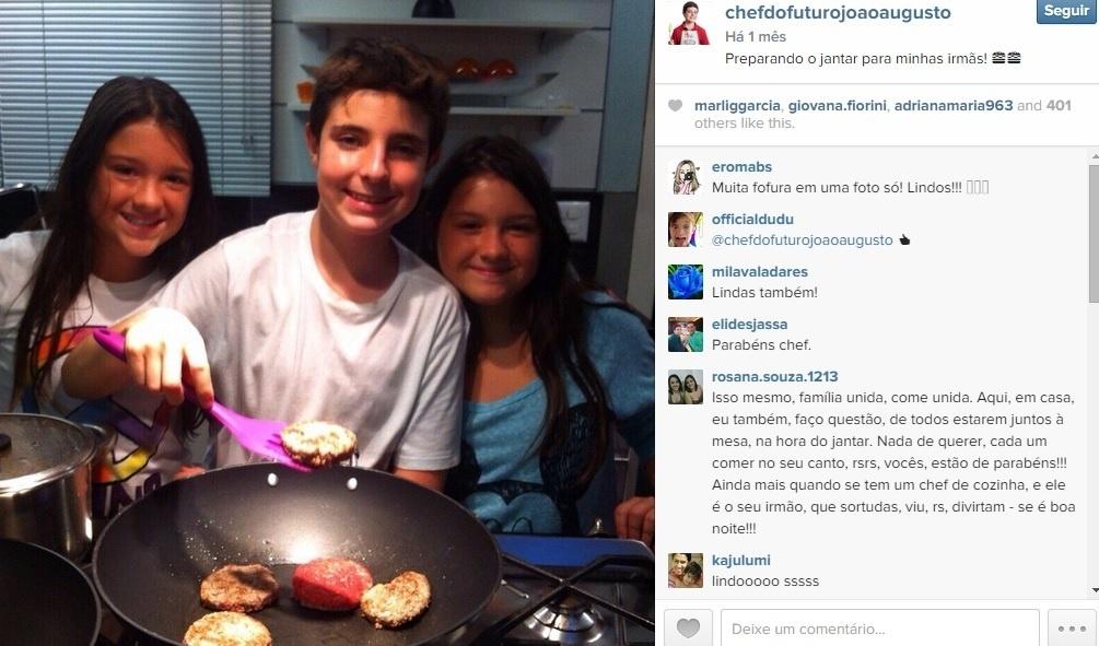 João Augusto prepara o jantar com as irmãs gêmeas na cozinha onde ele apresenta o