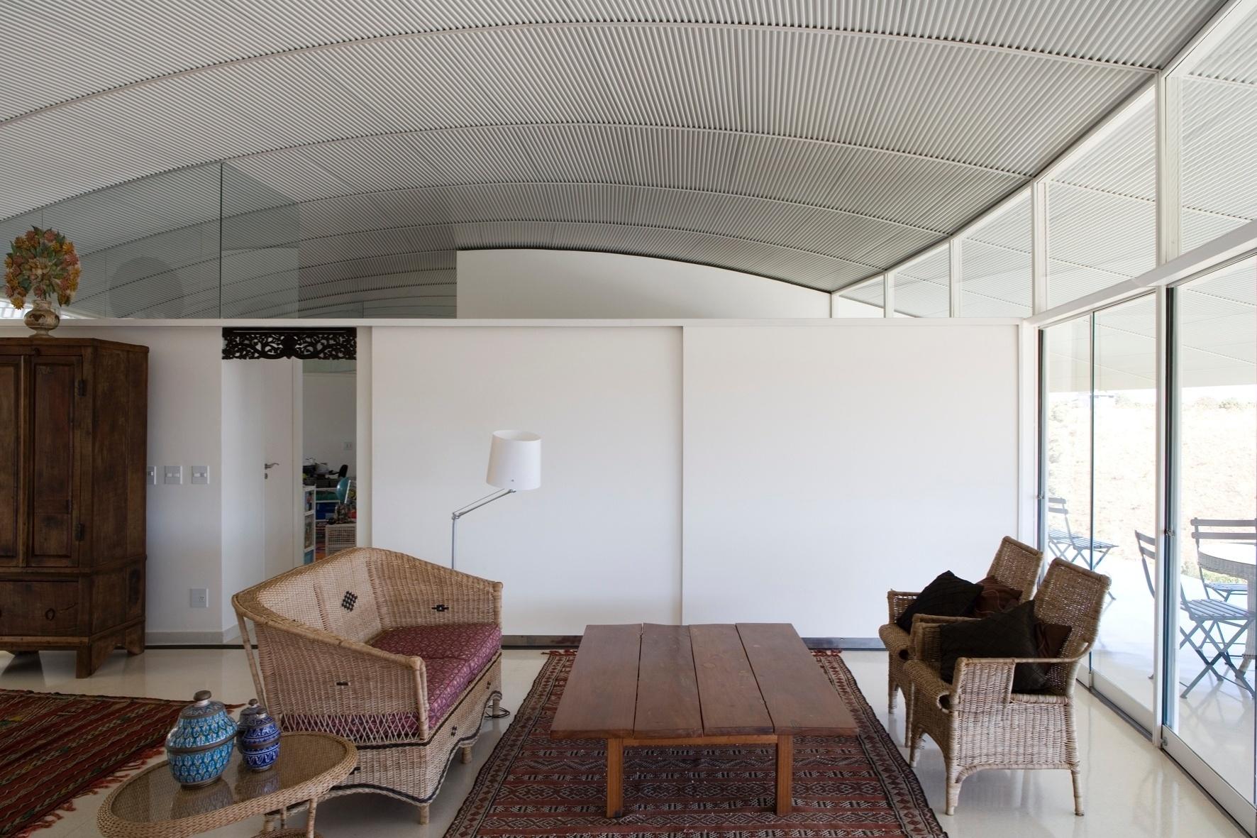 A decoração da sala de estar da casa RP, em Brasília (DF), é simples: tem base branca, piso claro e mobília que reúne madeira, fibras e tramas manuais (nos tapetes avermelhados). O projeto de arquitetura é assinado por João Filgueiras Lima, o Lelé