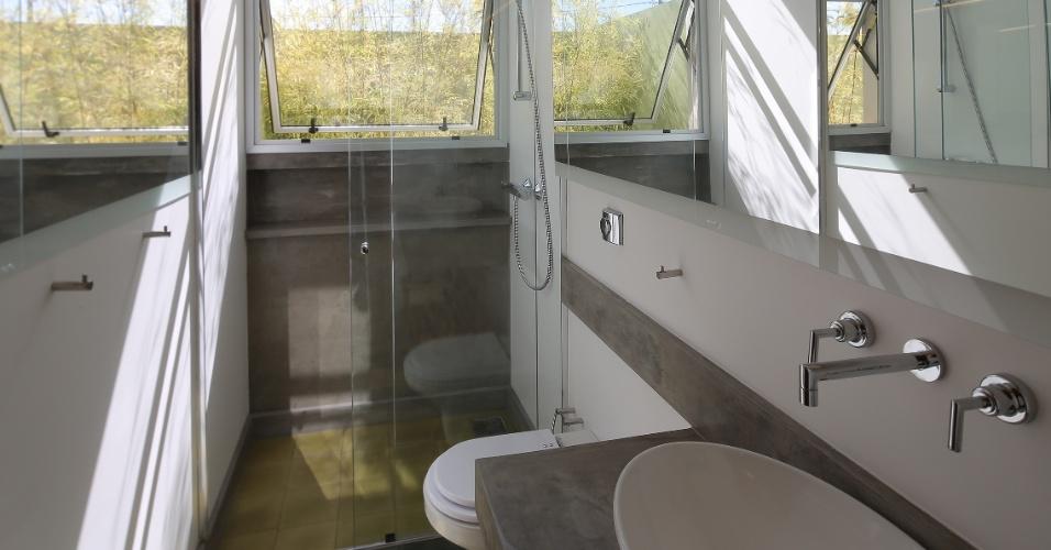 No banheiro, a pintura branca acrílica das paredes (PVC) é lavável. Os espelhos paralelos, iluminados por fitas LED, ampliam o espaço estreito e comprido. O piso é revestido por ladrilho hidráulico antiderrapante e os detalhes de bancada e das paredes acompanham a linguagem da casa Madrid, em concreto aparente. Louças e metais são da Deca e o projeto é da arquiteta Monica Drucker