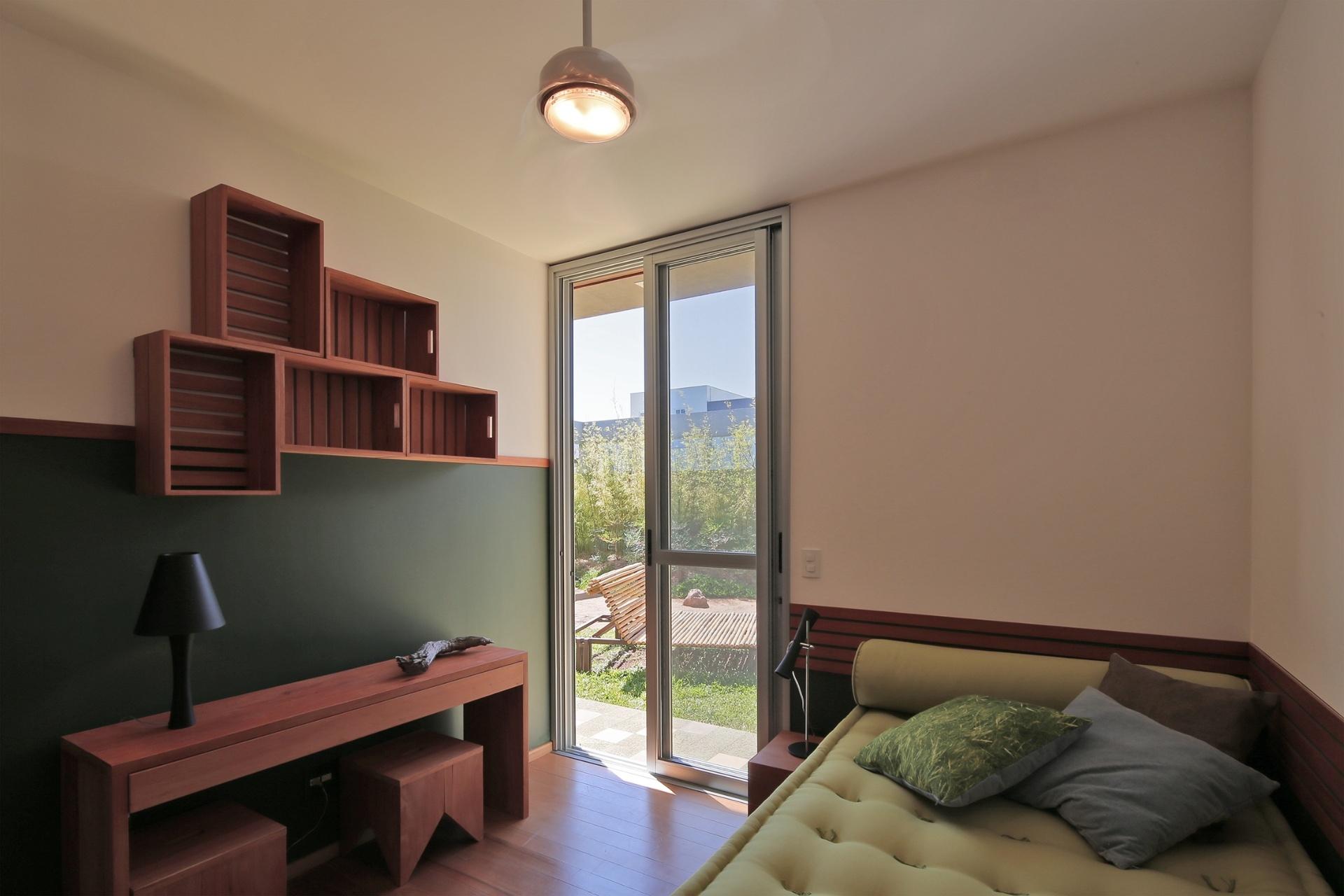 Todos os dormitórios se comunicam com pátio interno através de portas de correr. O piso é de tábuas de madeira cumaru e os móveis foram quase todos projetados pelo escritório Drucker Arquitetos Associados, que também assina a arquitetura da casa Madrid, em Marília (SP)
