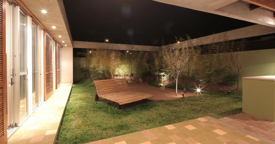 O pátio interno tem um jardim em estilo japonês. À direita, na área de churrasqueira (volume verde), o piso é intertravado e permeável, feito com concreto para acompanhar a linguagem arquitetônica: rústica, natural e com acabamentos simples. A casa Madrid é um projeto do escritório Drucker Arquitetos Associados e está em um condomínio residencial em Marília, interior de São Paulo