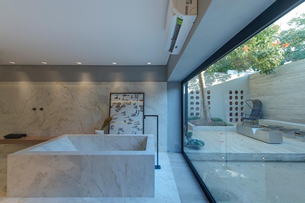 Casa Cor SP 2015 - Integrada ao ambiente externo por meio de um pano de vidro, a área de banho conta com banheira e revestimentos (parede e piso) em mármore. O espaço faz parte da Casa P&B, de Léo Shehtman