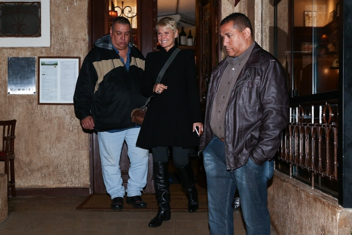 1.jun.2015 - Xuxa Meneghel deixa restaurante no Itaim Bibi, zona sul de São Paulo, na noite desta segunda-feira, acompanhada de dois seguranças