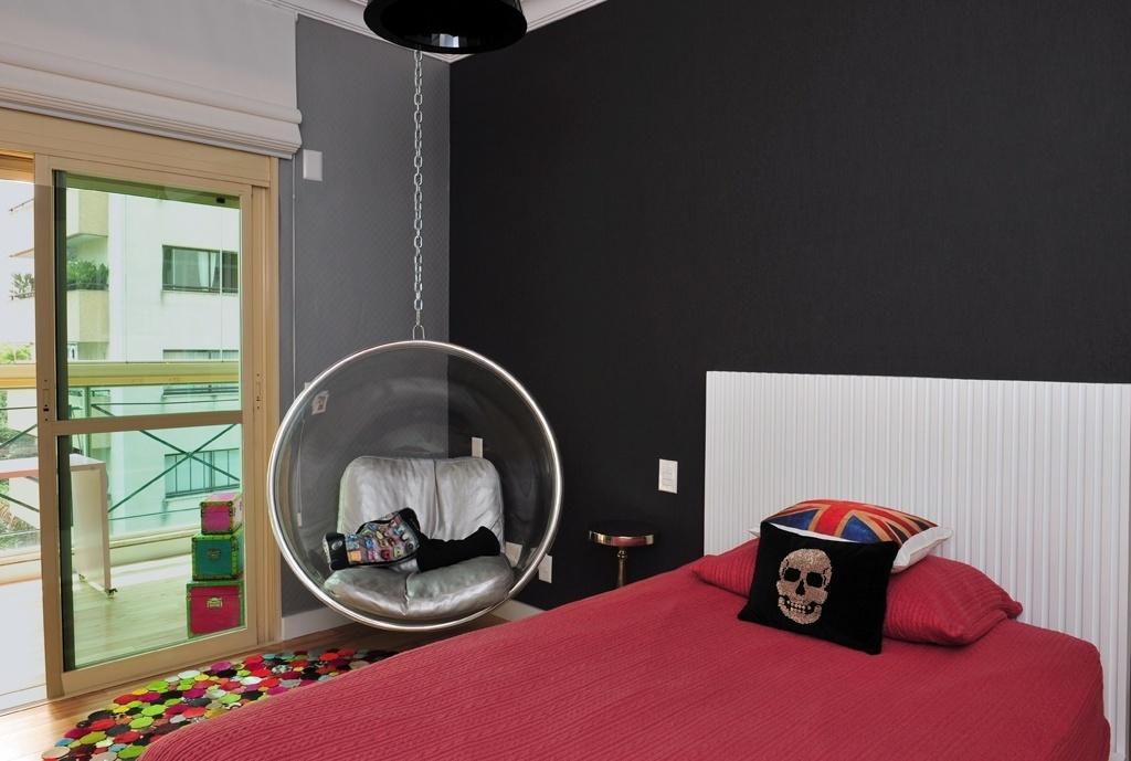 Com 18 m², este quarto foi pensado pela arquiteta Karina Korn para um adolescente de 17 anos, que desejava um espaço aconchegante e moderno. Pintado de preto e cinza, o ambiente recebeu cabeceira canelada branca e roupa de cama colorida. A poltrona de balanço cria um canto para o relaxamento ou para receber os amigos