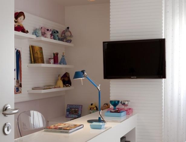Deste ângulo do dormitório planejado pela designer Cristina Barbara vê-se o canto de estudos que tem marcenaria versátil com nichos e prateleiras para os pertences, além de totem para TV. A cadeira Victoria Ghost Cristal é da Kartell