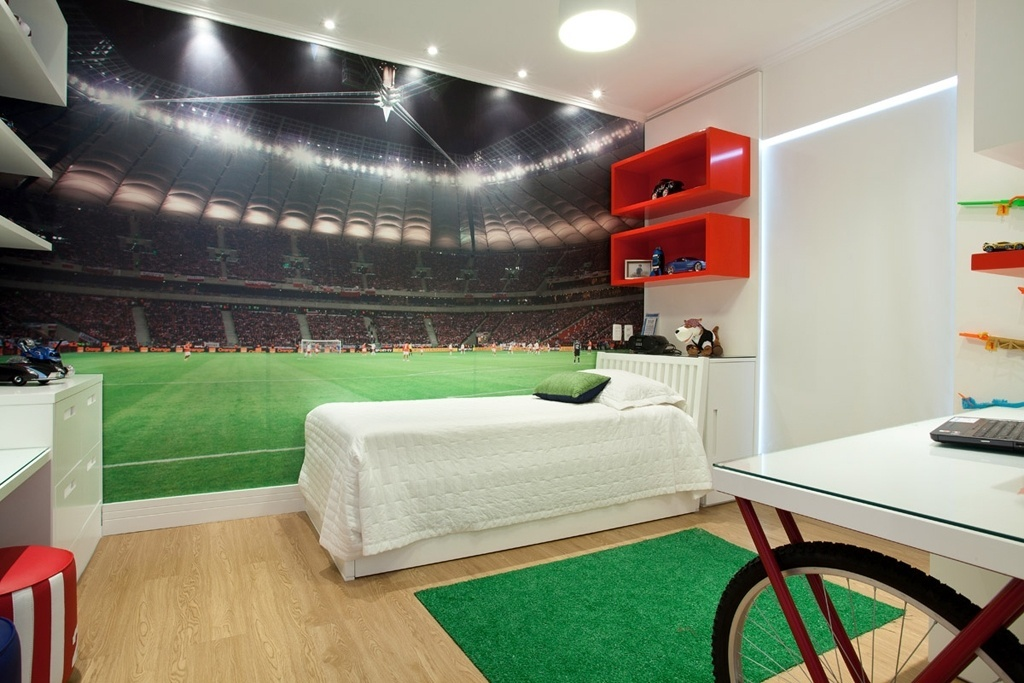 Esta reforma foi realizada pela arquiteta Raquel Kabbani, para um adolescente que gosta de fotos, tecnologia e futebol. Com 14 m², o quarto conta com uma foto de um estádio, móveis laqueados e tapete que lembra o gramado