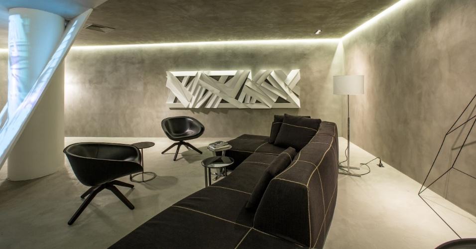 A sala de estar criada por Ricardo Bello Dias tem teto e paredes em cimento queimado. Para combinar com o acabamento neutro, poucas peças em branco e preto. O conceito é inspirado em um filme mudo, dirigido por Buster Keaton em 1920, intitulado
