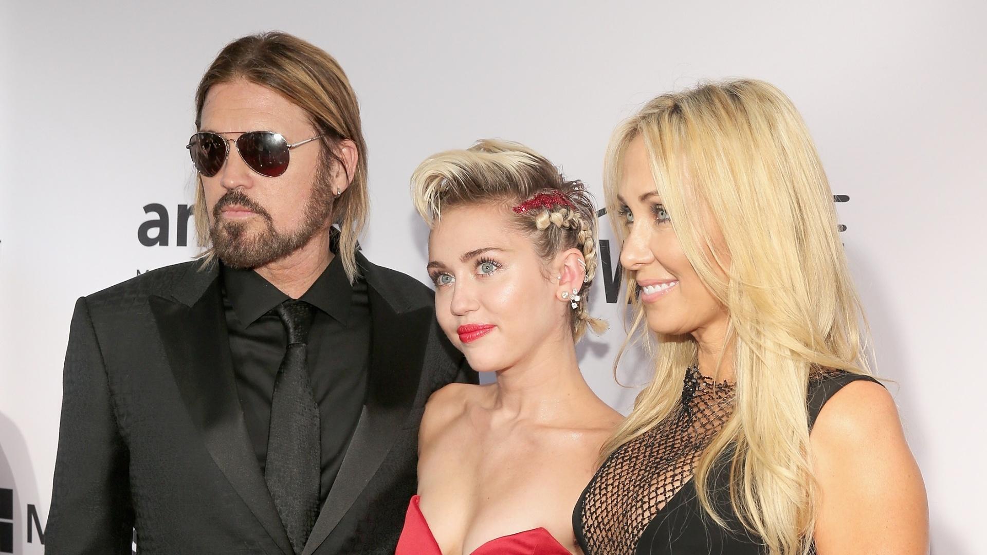 16.jun.2015 - Miley Cyru participa com os pais, o cantor Billy Ray Cyrus e a produtora Tish Cyrus, do Baile de Gala da amfAR de 2015