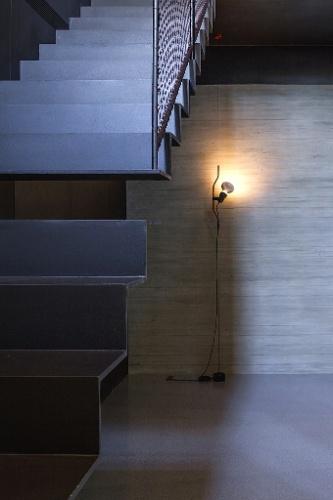Especialmente no andar subterrâneo do apartamento em Tel Aviv, a iluminação indireta - com focos de luz voltados para as paredes - aparece como elemento crucial ao refinamento da arquitetura industrial, com acabamentos escuros e rústicos. Destaque, ainda, para a leve escada