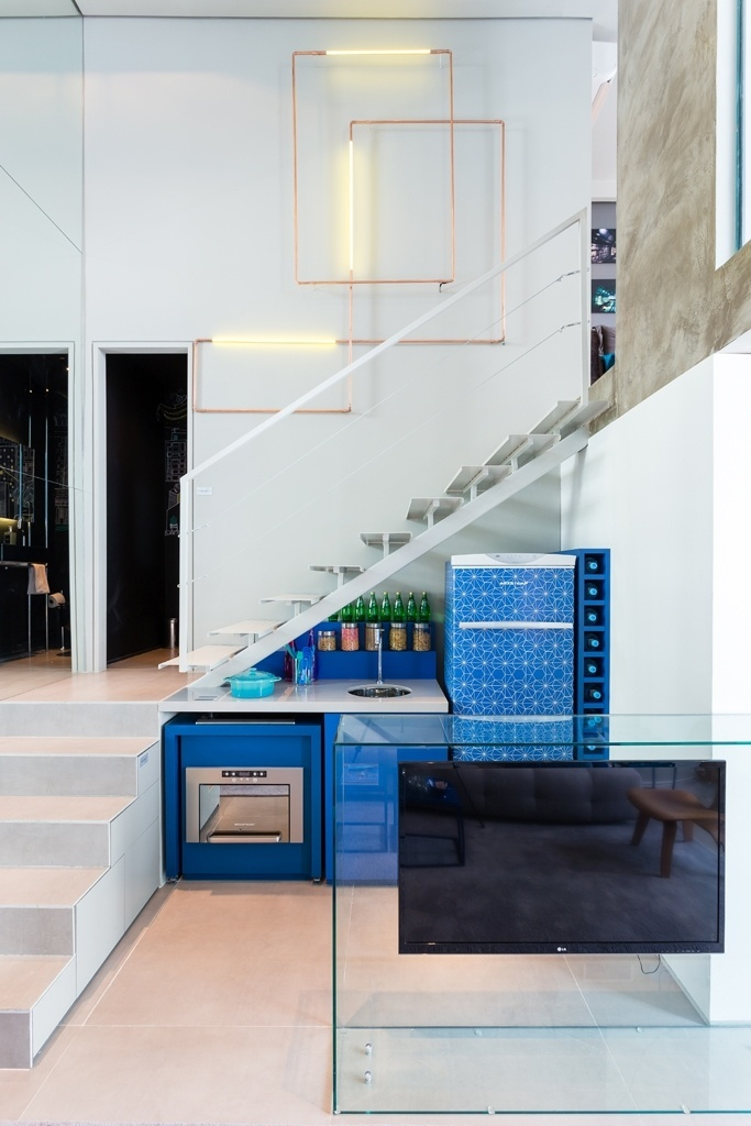 Com espaço limitado, o projeto de interiores desenvolvido pelo escritório Suite Arquitetos para o apê Alvorada quis gerar a sensação de amplitude, por isso as paredes laterais (à esq.) foram revestidas com espelhos. Os sistemas de divisão/ integração dos ambientes são inteligentes, a exemplo da caixa de vidro que serve como aparador de cozinha e móvel para TV