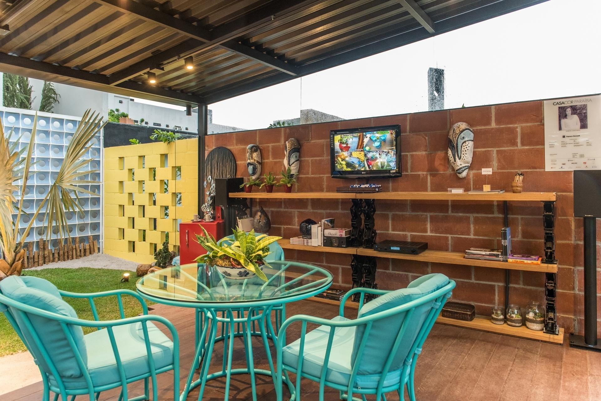 Casa Cor Paraíba 2016 - Pensado como uma típica varanda brasileira, o espaço criado por Dorita Santiago combina uma parede de tijolos aparentes a outras duas chamativas e coloridas, junto ao jardim. As estruturas vazadas são feitas de blocos de concreto pintados de amarelo e cobogós cerâmicos azuis