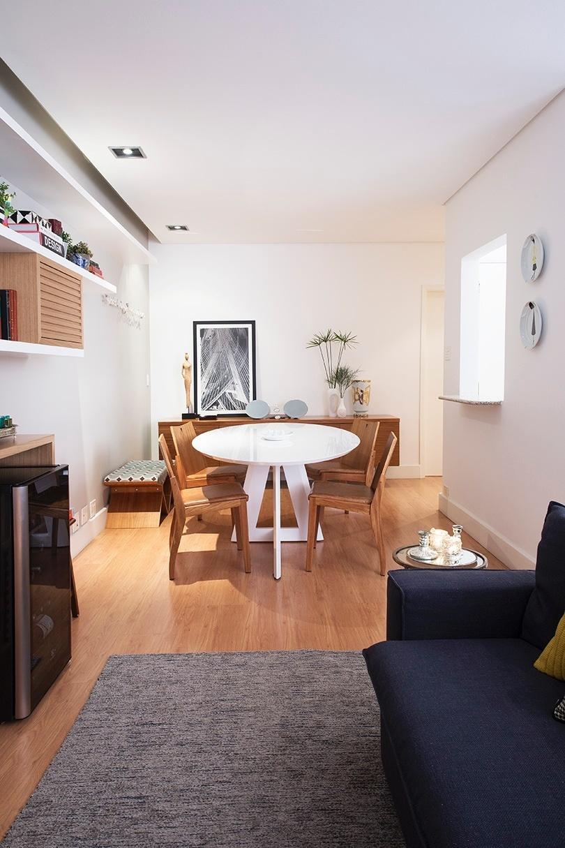 A mesa de jantar oval (Brentwood) tem pintura branca laqueada e seu formato amplia a circulação na área de refeições integrada. Em primeiro plano, o sofá azul marinho (Lider Interiores), sobre o tapete cinzento, marca a área dedicada à saleta de estar. O projeto de interiores é do escritório DN2 Arquitetura